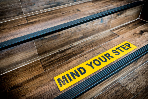 mind your step sticker sign pasted on wooden stair. warnings, abstract, or indoor architecture concept - fall prevention stock photos and pictures