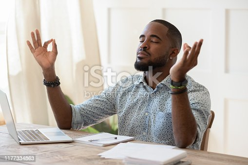 916126594 istock photo Mindful african american guy relaxing during remote working. 1177334863