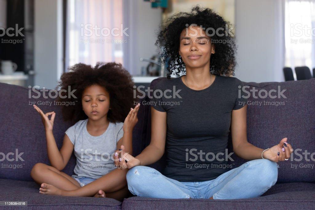 Indachtig Afrikaanse moeder met grappige jongen dochter samen yoga te doen - Royalty-free Aanraken Stockfoto