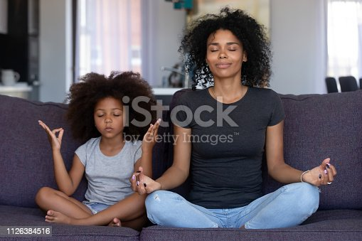 istock Mindful african mom with funny kid daughter doing yoga together 1126384516