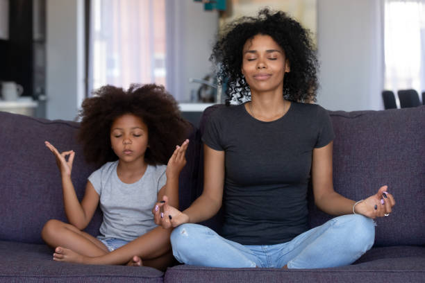 mindful african mom with funny kid daughter doing yoga together - w stanie zen zdjęcia i obrazy z banku zdjęć