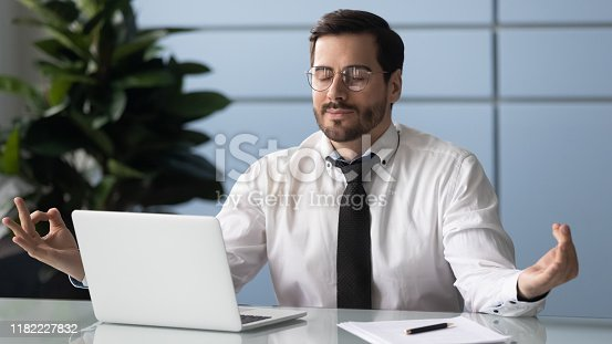 916520034istockphoto Mindful calm millennial businessman meditating at workplace. 1182227832