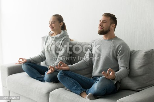 istock Mindful couple meditating together practicing yoga at home on so 916126594
