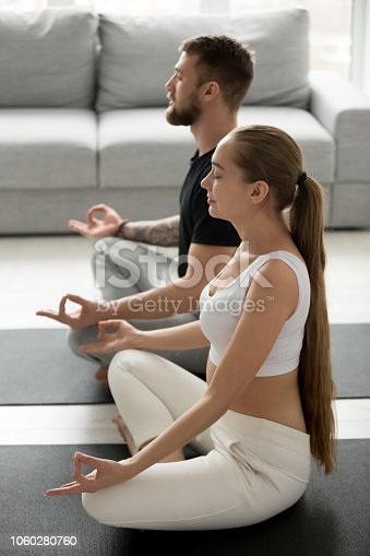 1060280760 istock photo Mindful man and woman practicing yoga on floor at home 1060280760
