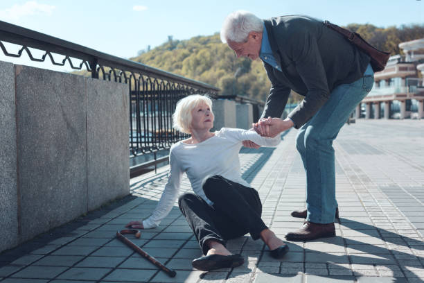 Mindful man helping elderly female stranger to stand up Thank you for helping me. Cheerful older male bypasser smiling while helping senior lady to stand up after falling to the ground during a daily walk. stranger stock pictures, royalty-free photos & images