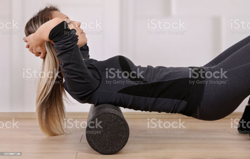 Mindful workout holistic health care. Woman doing foam roller exercises to relieve back pain stock photo