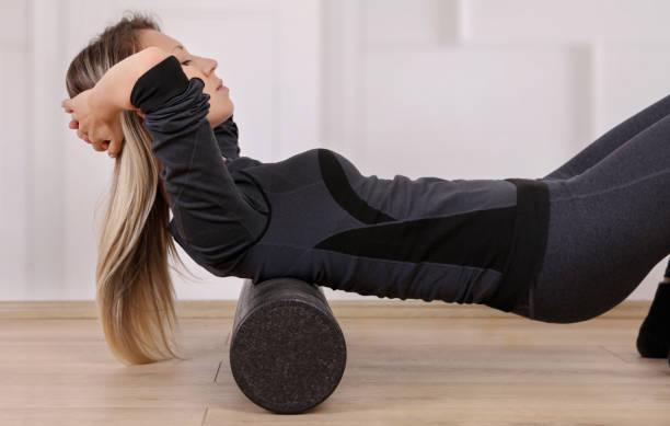 늘 운동 전체적 건강 관리입니다. 허리 통증을 해소 하기 위해 거품 롤러 연습을 하 고 하는 여자 - 굴리기 뉴스 사진 이미지