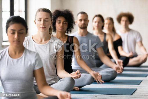 istock Mindful young mixed race people meditating indoors. 1262414093
