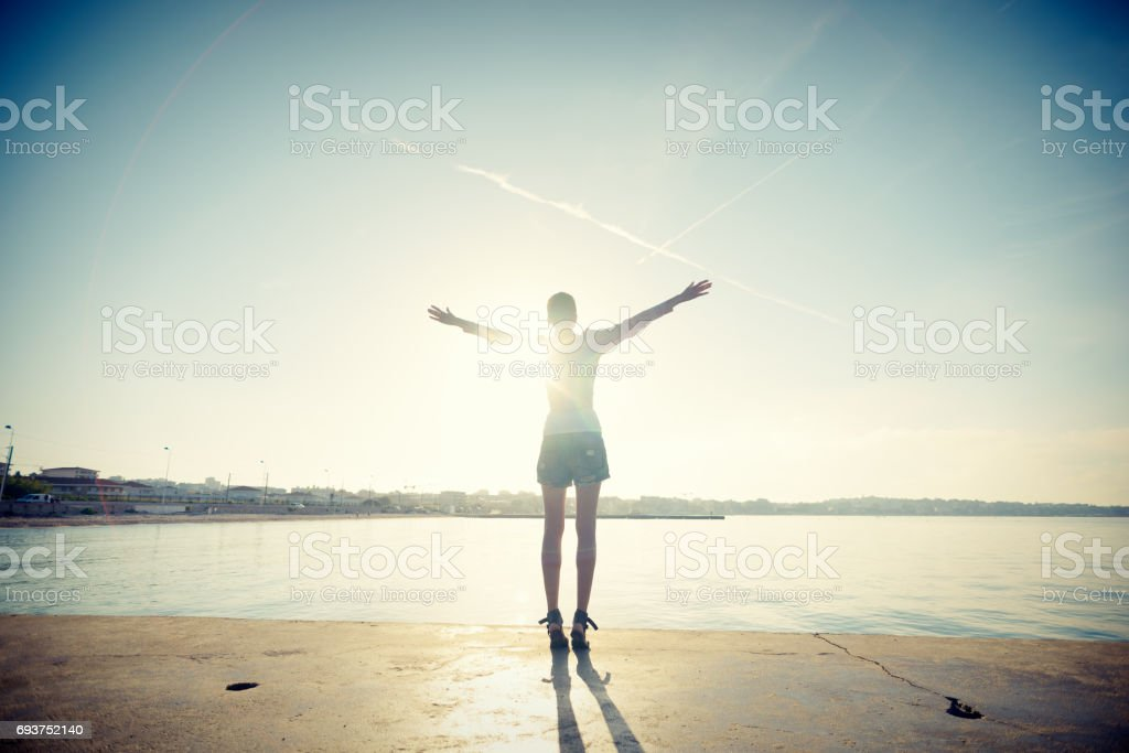 Mindful Young Woman Salutes Rising Sun at Ocean royalty-free stock photo