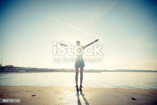 Mindful millennial woman by the ocean salutes the rising sun with outstretched arms. Shot from behind with long shadows and lens flare, Antibes Juan-les-Pins, Cote d'Azur, France.