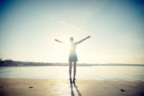 Mindful Young Woman Salutes Rising Sun at Ocean stock photo