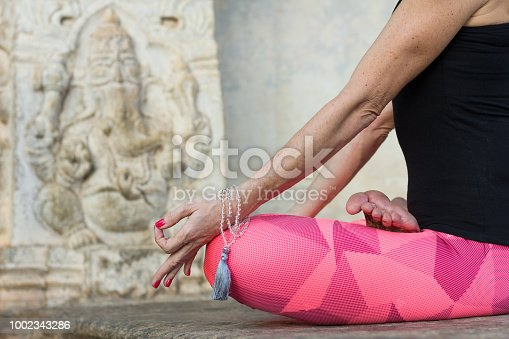 Yogi woman in padmasana pose with hands in chin mudra on knees, mala on wrist by Ganesha sculpture in Srirangapatna temple, Karnataka, India