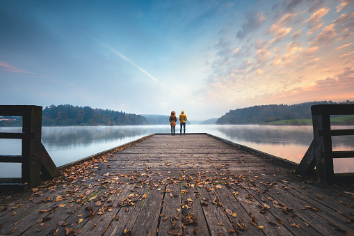 Young couple standing on the jetty and watching sunrise.