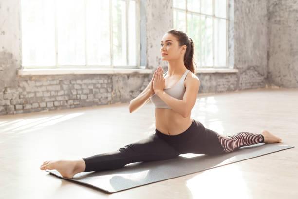 Mindfulness woman doing yoga at home doing split on mat hands in picture id1163630853?b=1&k=6&m=1163630853&s=612x612&w=0&h=c ylmzbbba tiro2pnuikexil861mqnc0kaf5xxnt6g=