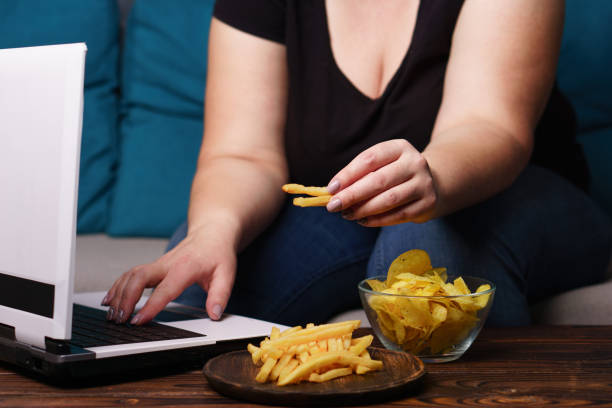 mindless snacking, overeating, lack of physical activity, lazine mindless snacking, overeating, lack of physical activity, laziness, homebody. . overweight woman engrossed in watching series at laptop eating fast food unhealthy eating stock pictures, royalty-free photos & images