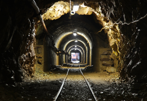 a mine tunnel. focus on the entering train.