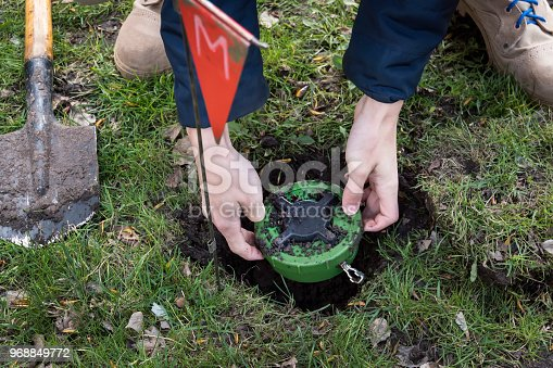 istock miner digs a mine. Demining of the territory. the guys digs a mine on a minefield. service in army. hazardous work. digging the ground with a sapper shovel 968849772