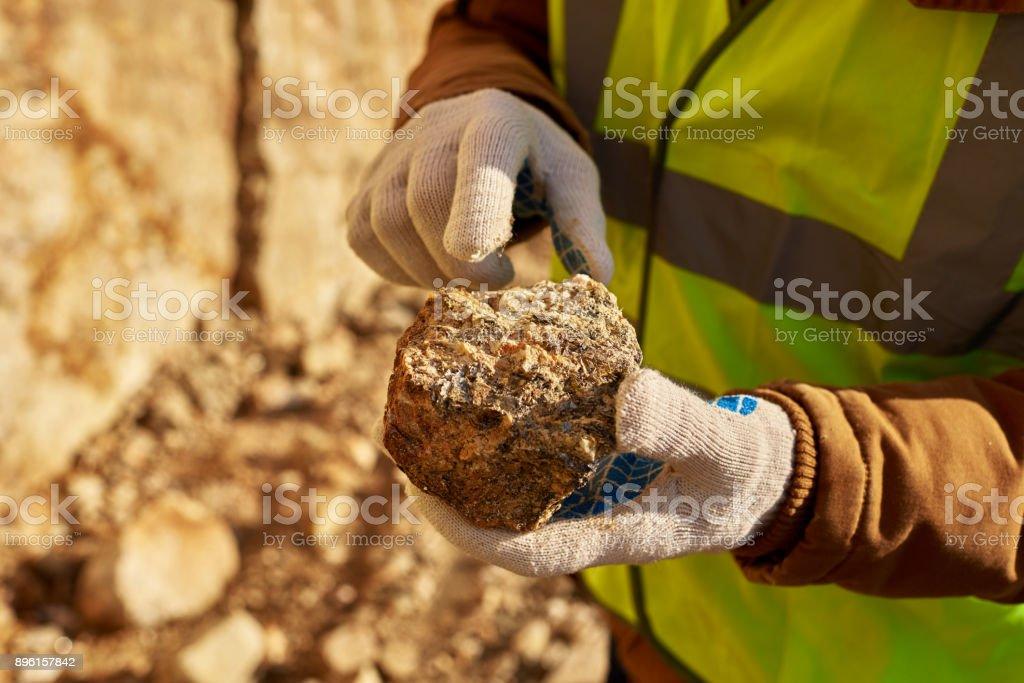Bergmann hält Stück Mineral – Foto