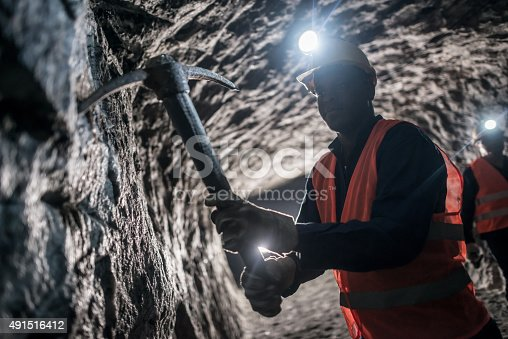 istock Miner using a pick tool at the mine 491516412