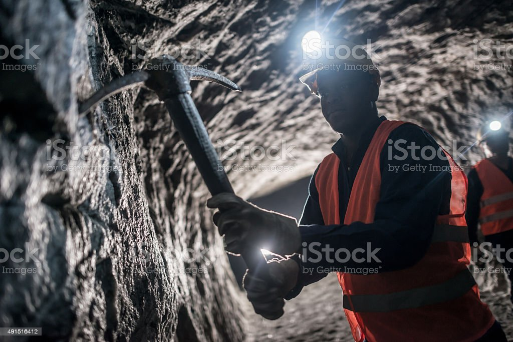Miner using a pick tool at the mine stock photo