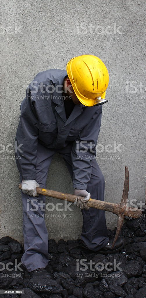 Miner using a pickaxe stock photo