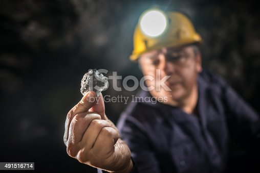 508140747 istock photo Miner working and holding a piece of rock 491516714