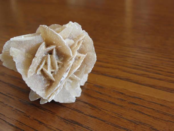 minéral du désert rose sur la table en bois. également connu sous le nom sable rock rose ou rose ou rose sélénite, gypse rose ou baryte rose. - rose des sables photos et images de collection