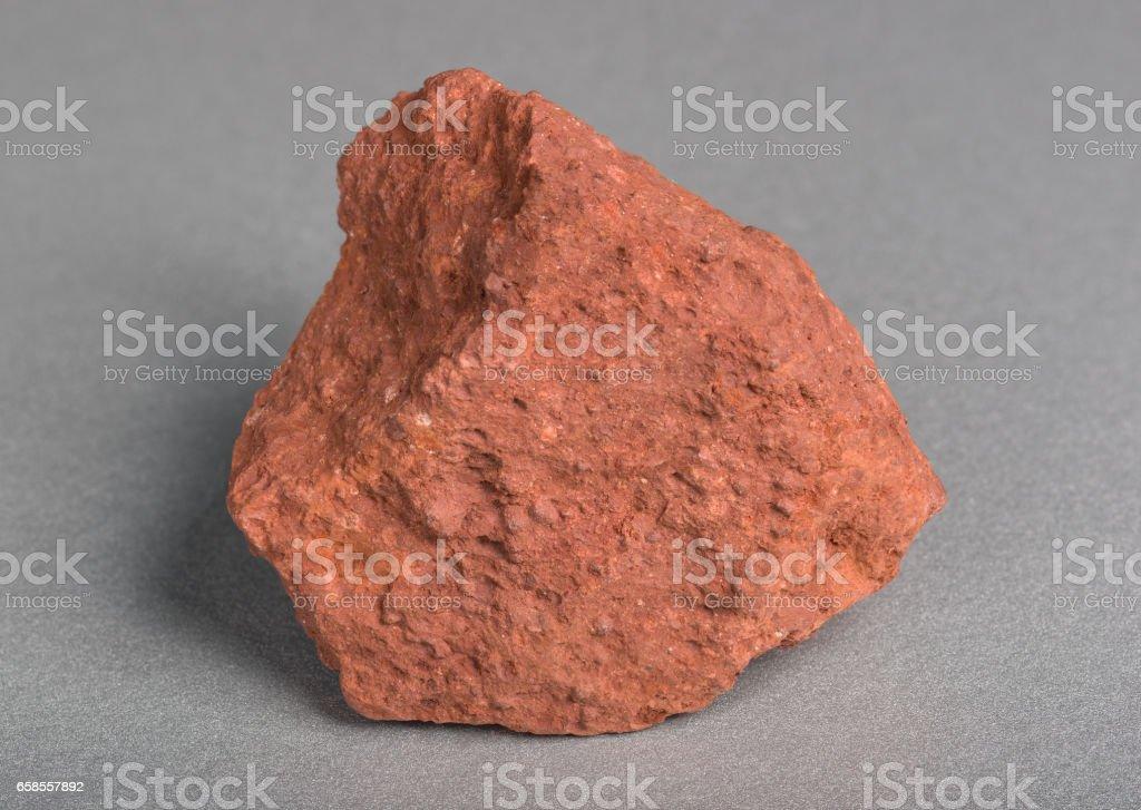 Minéraux Pierre bauxite sur fond gris. Bauxite, un minerai d'aluminium, est la principale source d'aluminium. - Photo