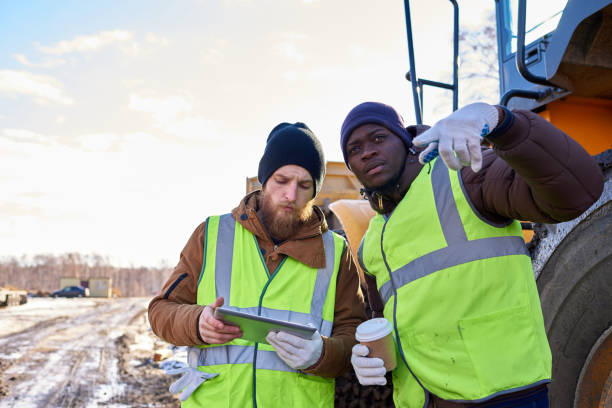 Miners Crew on Site Portrait of two workers, one African-American, drinking coffee and using digital tablet standing next to heavy industrial truck on worksite, copy space frontier field stock pictures, royalty-free photos & images