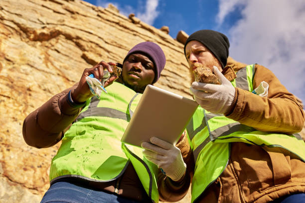 Miners Inspecting Worksite Searching for Minerals Low angle portrait of two industrial workers wearing reflective jackets, one of them African, inspecting mineral ore on site outdoors and using digital tablet frontier field stock pictures, royalty-free photos & images