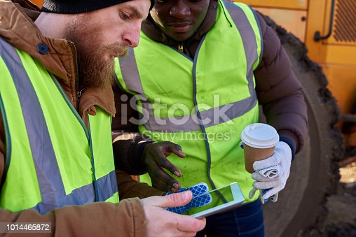 Mid section portrait of two workers, one African-American, using digital tablet standing next to heavy industrial truck on worksite