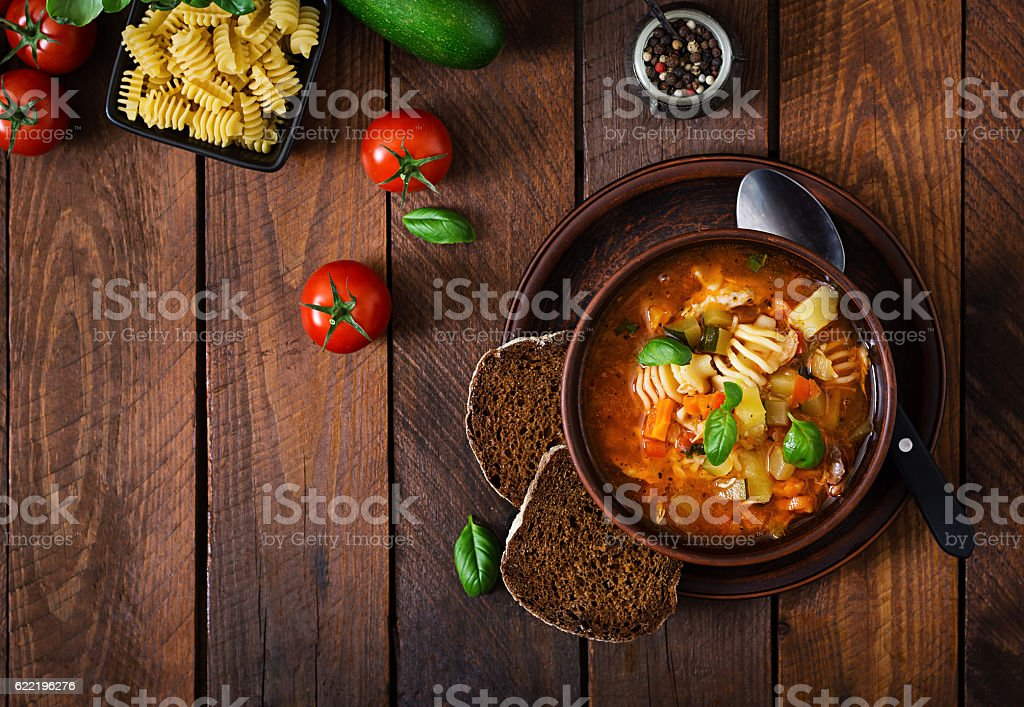 Minestrone, italian vegetable soup with pasta on wooden table stock photo