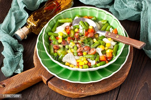 Ceramic bowl of soup minestrone with seasonal vegetables on wooden table. Dish of italian cuisine