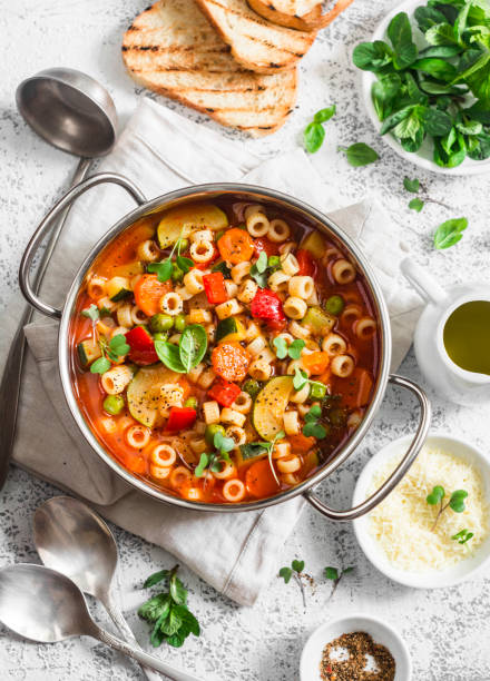 minestrone soup in a pan on a light table, top view. delicious vegetarian food concept. flat lay - minestrone foto e immagini stock