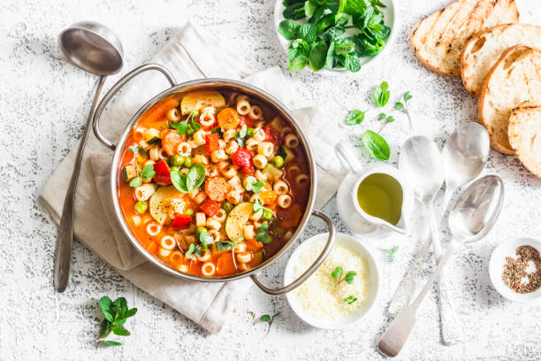 minestrone soup in a pan on a light table, top view. italian soup with pasta and seasonal vegetables. delicious vegetarian food concept. flat lay - minestrone foto e immagini stock