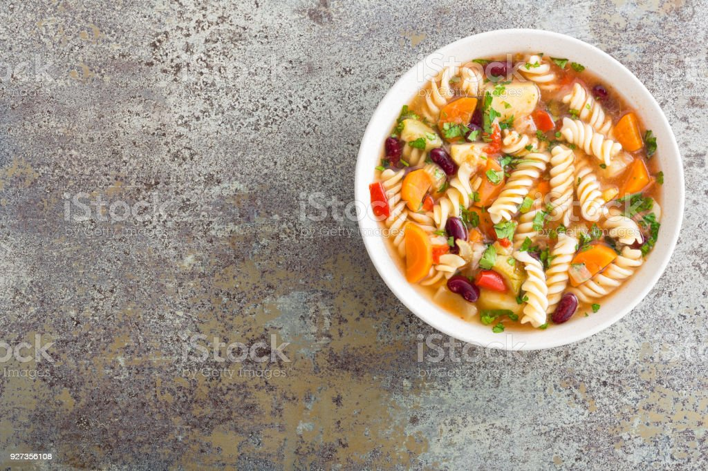 Minestrone soup. Vegetable soup with fresh tomato, celery, carrot, zucchini, onion, pepper, beans and pasta. Dish of italian cuisine. - Royalty-free Bean Stock Photo