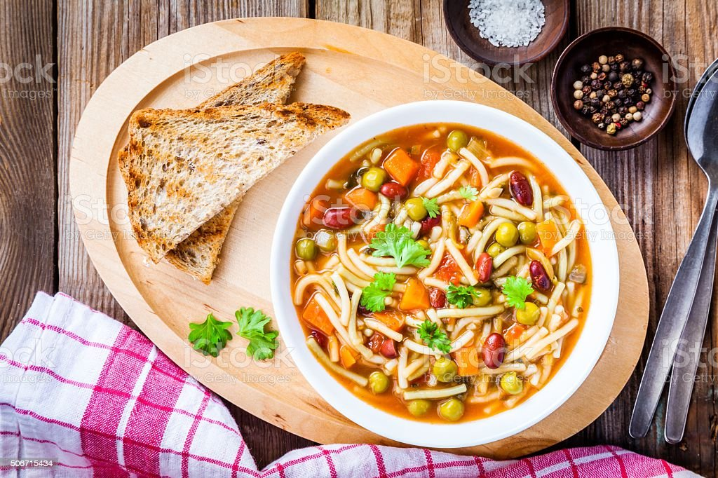 Minestrone soup with whole grain toasts stock photo