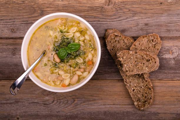 minestrone with fresh pesto and brown seeded bread. - minestrone foto e immagini stock