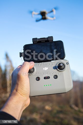 Schmitten, Germany - November 25, 2020: Camera drone Mini 2 and controller of Chinese technology company DJ Innovations (DJI).  DJI Mini 2 is a high-performance camera drone with a very small, portable design in the safest drone category weighing less than 249 grams. It is the successor to DJI's original Mavic Mini. DJI was founded in 2006, it produces unmanned, remote controlled aerial vehicles for many fields of application, e.g. aerial photography and videography.