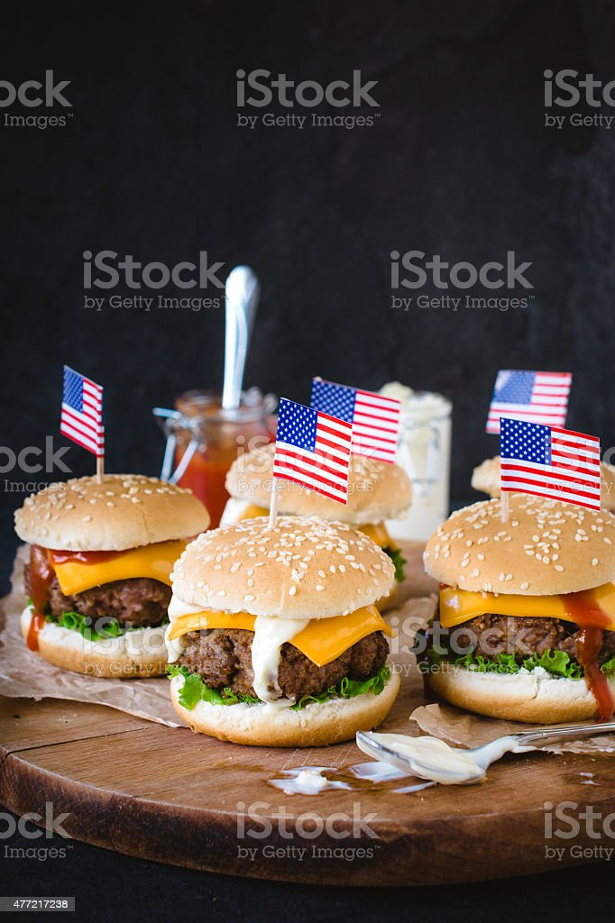 Mini ground beef burgers with American flag on wooden...