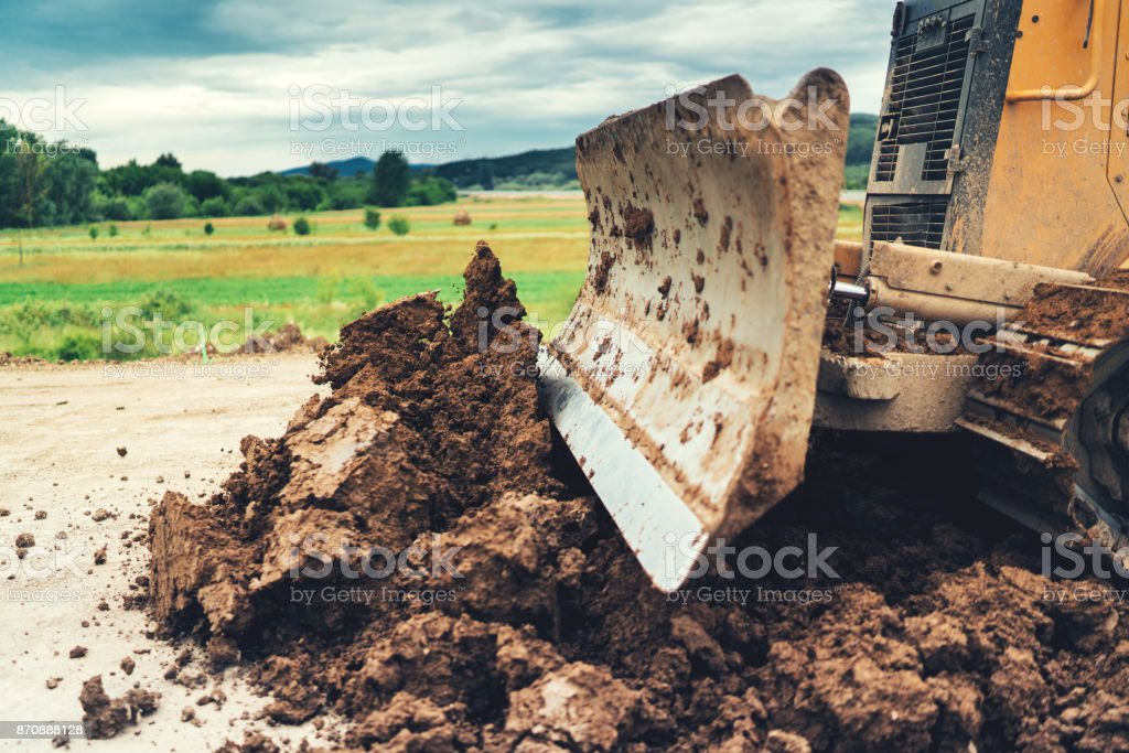 mini bulldozer doing landscaping works during house construction site stock photo