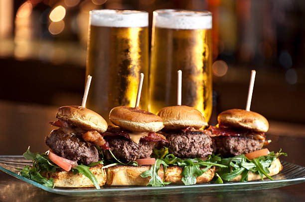 mini burgers and beer - sliding stock photos and pictures