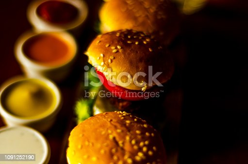 mini burgers with meat, vegetables, cheese and other toppings, bread sprinkled with sesame seeds, mini fast food, tasty set