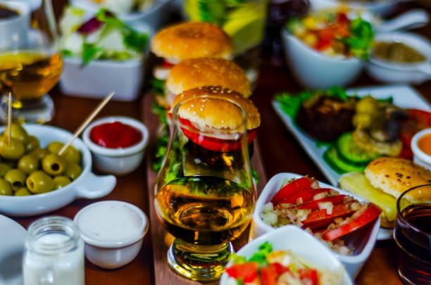 mini hambúrgueres com carne, legumes, queijo e outros recheios, pão polvilhado com sementes de gergelim, mini fast-food, - foto de acervo