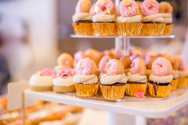 Mini chocolate cupcakes topped with mini pink donuts on a dessert table. They are displayed on a tiered display tray. Mini chocolate cupcakes topped with mini pink donuts on a dessert table. They are displayed on a tiered display tray. buttercream stock pictures, royalty-free photos & images