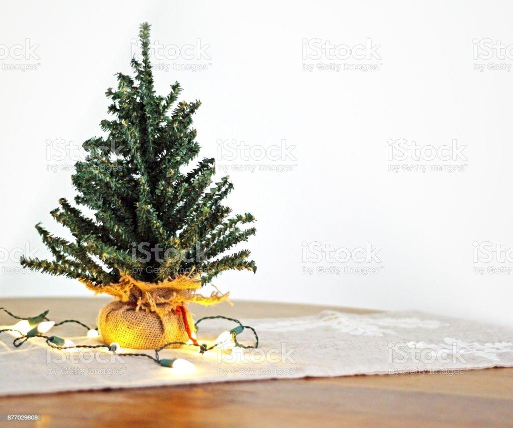 mini christmas tree with lights on seasonal table runner royalty free stock photo