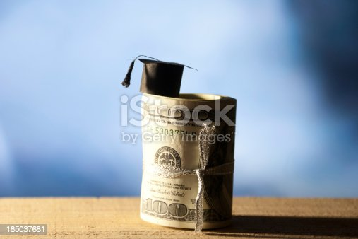 941829872 istock photo Mini college graduation cap on cash. 185037681