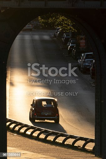 Hamburg, Germany - May 21. 2018:A Mini Cooper car drives on the road at sunset, near the port of Hamburg. In the foreground, you can see an archway from a railway overpass