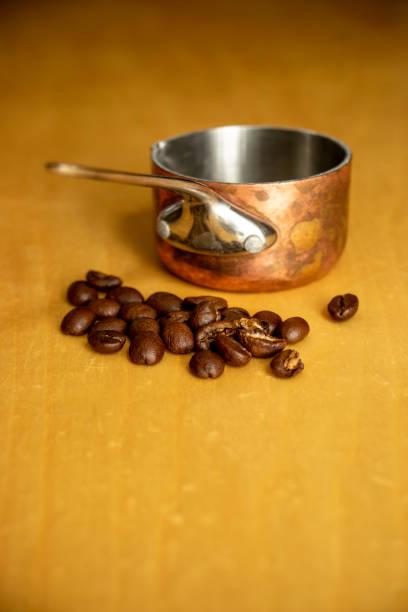 Mini copper saucepan and coffee beans stock photo