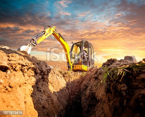 Mini Excavator. Yellow mini excavator on the construction site. Excavator operator chooses the ground for the foundation. Mini digger digs down in the background of the sunset.